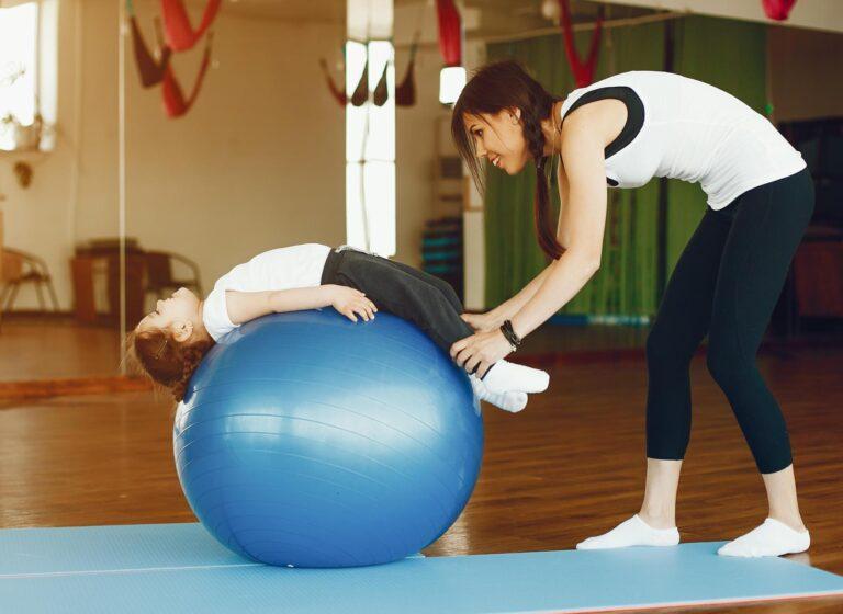 Una bambina svolge degli esercizi con la fitball